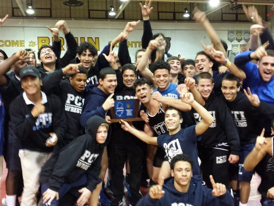 Coach Luis Colon (center) holds the trophy after his