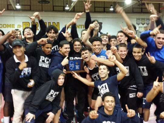 Coach Luis Colon (center) holds the trophy after his Passaic Tech team won the North 1, Group 5 tournament.