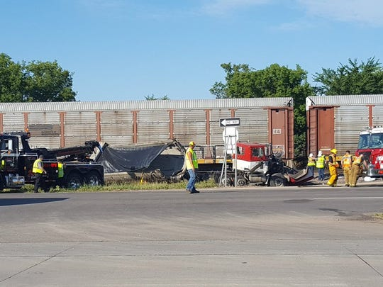 Fire crews roll up a hose as a tow truck gets into place beside a trailer that collided with a train Monday, July 31, at U.S. Highway 10 and 32nd Street Southeast.