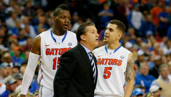 ATLANTA, GA - MARCH 16:  Head coach John Calipari of the Kentucky Wildcats yells to his team as Will Yeguete #15 and Scottie Wilbekin #5 of the Florida Gators look on in the second half during the Championship game of the 2014 Men's SEC Basketball Tournament at Georgia Dome on March 16, 2014 in Atlanta, Georgia.  (Photo by Kevin C. Cox/Getty Images)