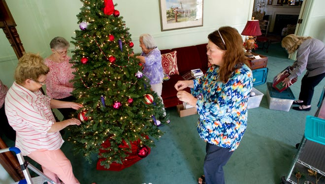 Women decorate a Christmas tree at the Abilene Woman's Club at 3425 South 14th St. in preparation for their annual home tour.