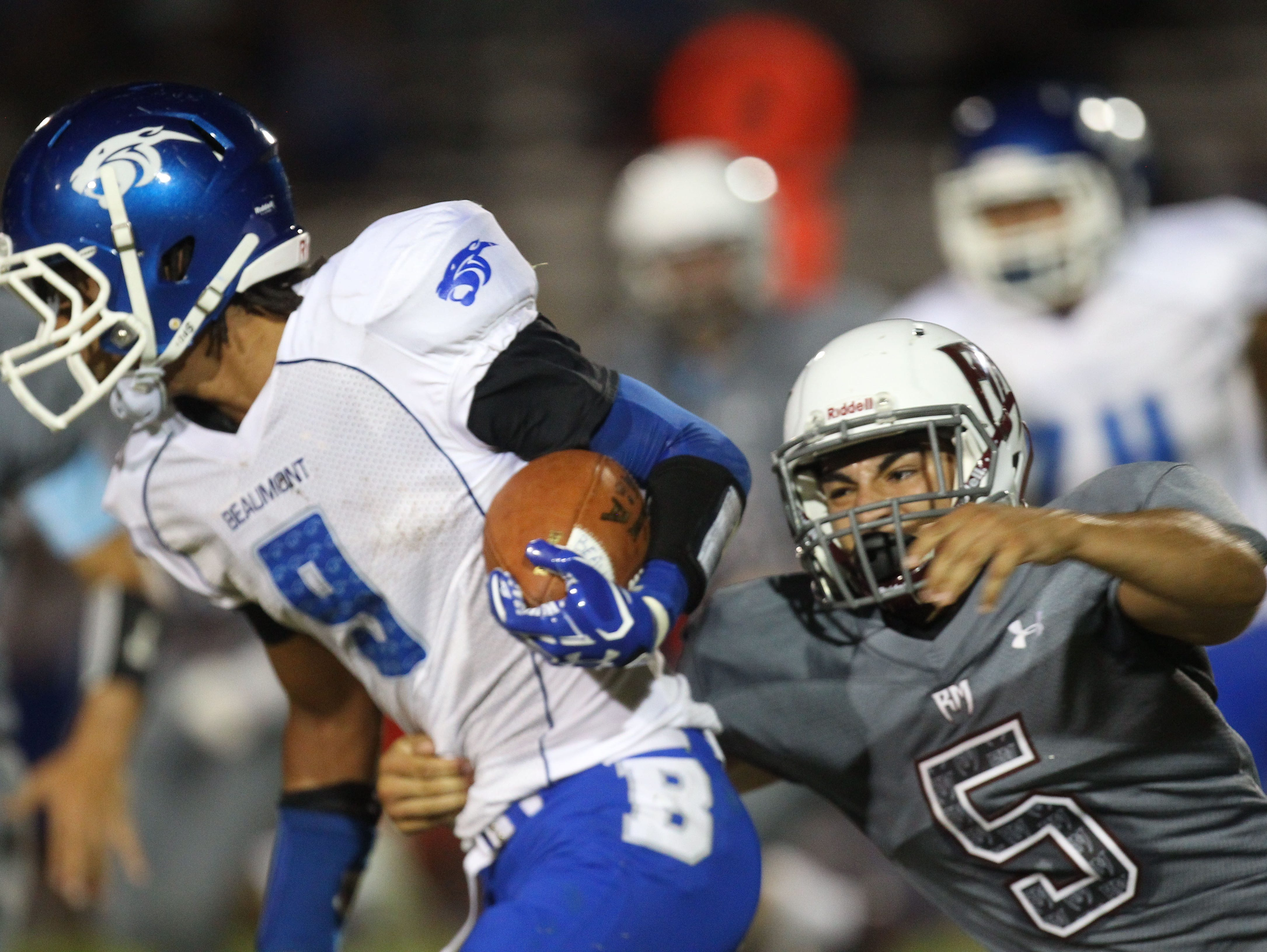 At right, Rancho Mirage High School's Michael Ramos makes a tackle in the first half of their game at home against Beaumont.