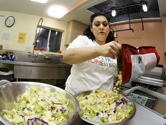 Volunteer Angie Torrez prepares a dinner salad for