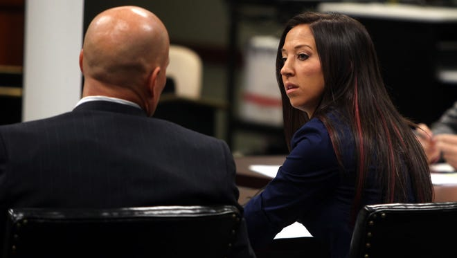 Former Cincinnati Ben-Gal and Dixie Heights High School teacher Sarah Jones,  charged with first degree sexual abuse for alleged sexual contact with a student, talks with her attorney Eric Deters before a suppression hearing in Kenton Circuit Court in Covington, Ky.