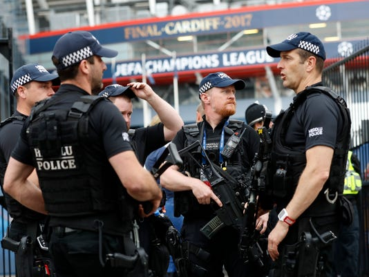 Armed police officers stand guard outside the Millennium Stadium in Cardiff, Wales, Friday June 2, 2017, ahead of Champions League soccer team training sessions. Real Madrid will play Juventus in the final of the Champions League soccer match in Cardiff on Saturday. (AP Photo/Frank Augstein)