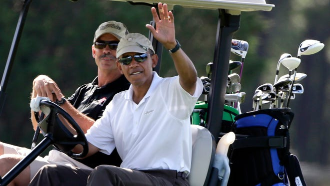 President Barack Obama, right, waves to a crowd of onlookers while driving a golf cart with businessman Glenn Hutchins as they golf at Farm Neck Golf Club in Oak Bluffs, Mass., on the island of Martha's Vineyard, Saturday.