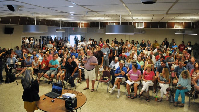 A line formed of people asking questions of the experts. Over 200 people packed the Satellite Beach Civic Center on Sunday for a meeting concerning cancer data collection and water test results. Several speakers addressed the audience.