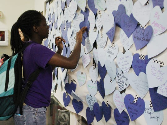 """As a part of Leon High School's """"Anti-Bullying Week,"""" students left positive messages on blue hearts to students. Kiara Holes, 16, attaches a message to the wall."""