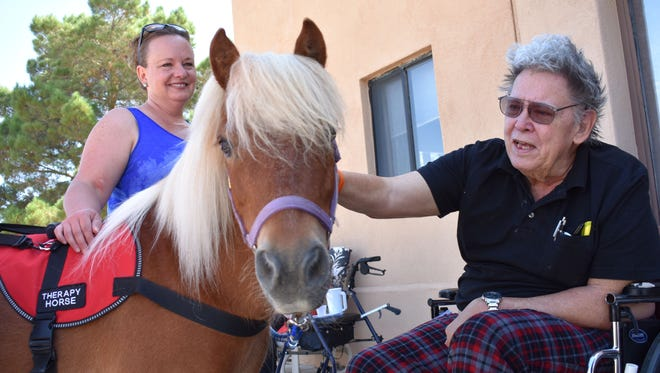 Red, a miniature therapy horse, visits with John Koval at Casa Arena Blanca Nursing Center on Tuesday morning.