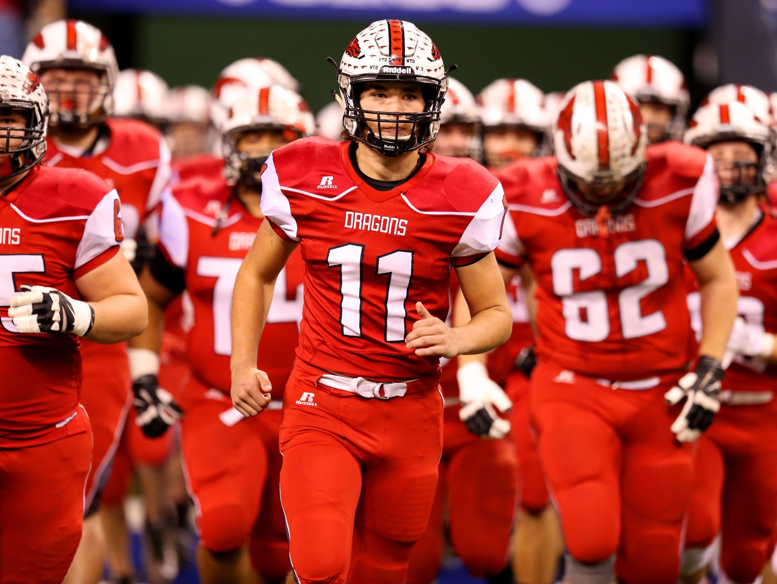 New PalestineÕs Alex Neligh (11) leads his team onto the field before playing Fort Wayne Snider at Lucas Oil Stadium on Nov. 27, 2015.