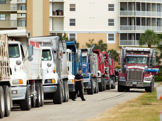 In this October 2013 file photo, dump trucks line up at a staging area during a beach renourishment project at Vanderbilt Beach in Naples.