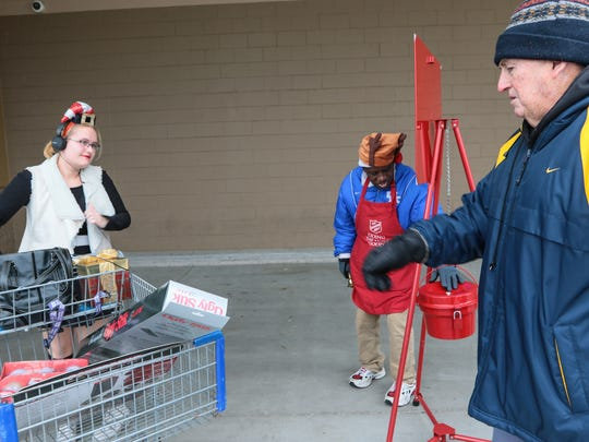 """McKenzie Miller, left, of Anderson gets ready to donate money at a Salvation Army Red Kettle with James Robert """"Radio"""" Kennedy and Harold Jones, right, of Anderson on Saturday at the Sam's Club in Anderson."""