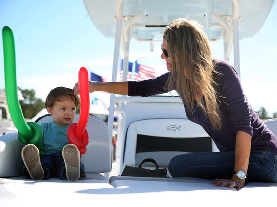 Jase Salrin, left, 2, sits in a boat with his mom, Amy Salrin, right, at the Naples Boat Show on January 29, 2015, at the Florida Sports Park in Naples.