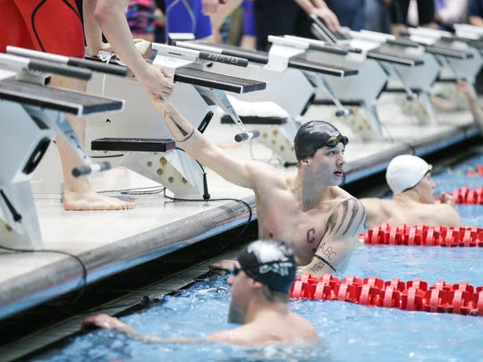 Carmel's Drew Drew Kibler is congratulated after the 200 yard freestyle relay team takes first, during the 2017 IHSAA High School Boys Swimming and Diving State Finals, held at the IUPUI Natatorium, Feb. 25, 2017.
