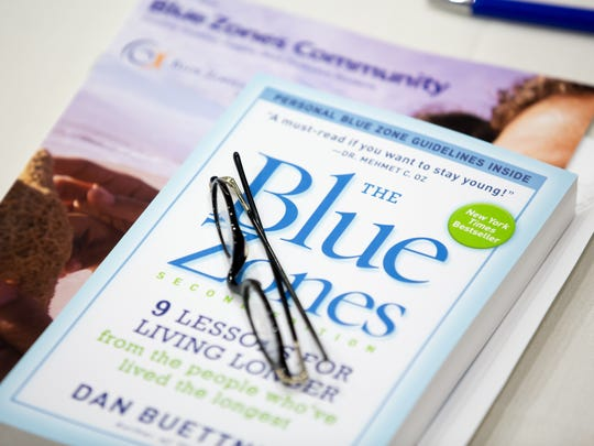 A copy of The Blue Zones sits on a table during a presentation