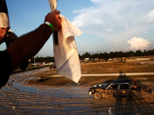 Matt Sherwood signals racers that they are entering their final lap at the 23rd annual Crash & Bash Demolition Derby at the Collier County Fairgrounds on Saturday, August 23, 2014.