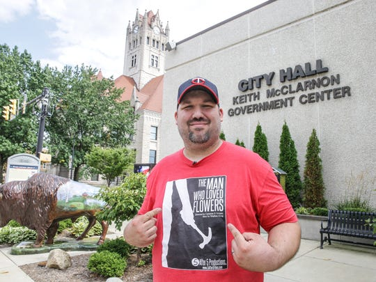 "Five after Five Productions Director Cameron Grimm shows off his move shirt for his newest project ""The Man Who Loved Flowers"" along Main S. in Greenfield on Wednesday, August 30, 2017. The film is based on a short story by Stephen King and will film in Greenfield starting in September."