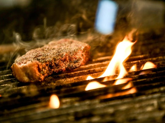A steak cooks on the grill at Provision, a new restaurant located inside the Ironworks Hotel in Indianapolis on Friday, Sept. 8, 2017. The upscale restaurant is part of the Cunningham Restaurant Group.