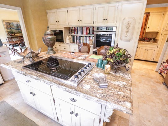 A kitchen island with range and recessed oven offer