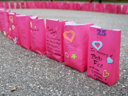 Pink bags honoring loved ones form a ribbon near the