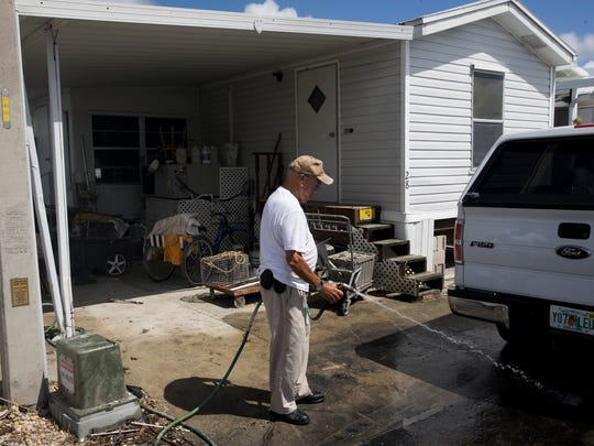 "Rod Pascual, 88, washes mud from his driveway in Fisherman's Cove Mobile Home Park Tuesday, October 3, 2017 in Everglades City, Fla. A significant number of Pascual's neighbors homes are condemned to be torn down, demoed due to damage from Hurricane Irma. Pascual, along with his three sons, ripped out all of the insulation and duct work inside his home. ""Been here 30 years,"" Pascual said. ""It's gonna take some time but we're gonna get it."""