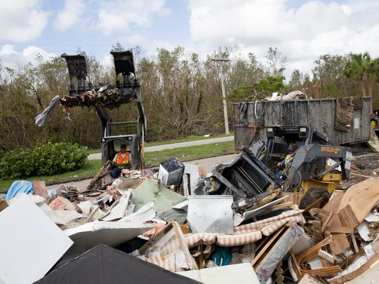 Crews work to clear trash and debris outside of Fisherman's Cove Mobile Home Park along Copeland Avenue Tuesday, October 3, 2017 in Everglades City, Fla.