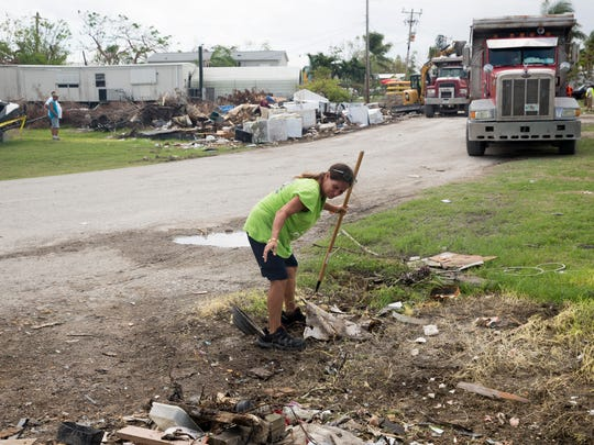 Crystal Holler consolidates the remaining leftover trash in her front yard as dump trucks continue to haul off roadside trash along her street Tuesday, October 3, 2017 in Chokoloskee, Fla.