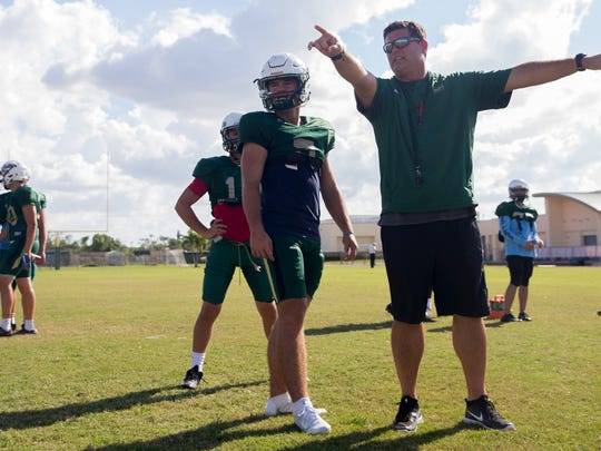 Jensen Jones, the junior quarterback for St. John Neumann High School, and head coach Damon Jones, also Jones' father, talk routes during practice at St. John Neumann's Monday, October 9, 2017 in East Naples. Jones, who is playing his first year at quarterback, has played a large role in leading the team to an undefeated 4-0 start to the season.