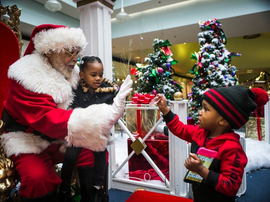 """December 20, 2017 - Raymond Conley, 65, holds Zendiya Smith, 3, as he high fives her brother Zaire Smith, 1, during their visit to Southland Mall on Wednesday. Conley, who works for Cherry Hill Photo, has been portraying Santa Claus at the mall for seven years. """"I'm Santa Claus – the only one,"""" Conley said. """"I have fun with it. Santa loves the kids."""""""