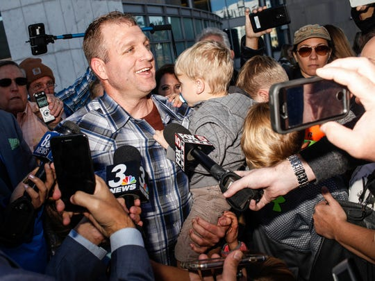 Ammon Bundy embraces his children outside the courthouse in Las Vegas on Nov. 30, 2017, after being released from custody.