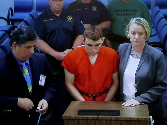 A video monitor shows school shooting suspect Nikolas Cruz, center, making an appearance before Judge Kim Theresa Mollica in Broward County Court, Thursday, Feb. 15, 2018, in Fort Lauderdale.