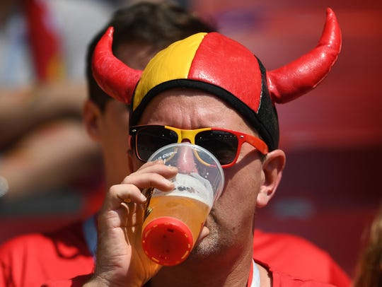 A Belgium fan drinks a beer ahead of the Russia 2018