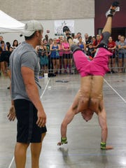 Mark Fuslier (right) completes a max handstand walk as he and his partner Robbie Roberts (left) compete in the Battle of the Fittest held at the Riverfront Center in downtown Alexandria. In addition to the handstands, they also had to complete 60 pistols and 200 double unders.