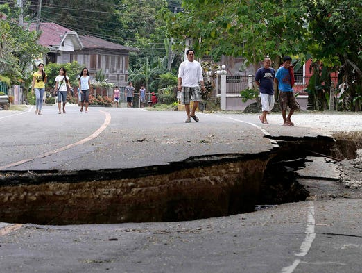 People walk on a highway damaged during a magnitude-7.2 earthquake on Oct. 16 in Loboc township, Philippines. A massive earthquake struck Cebu province on Oct. 15, destroying buildings, roads and bridges.