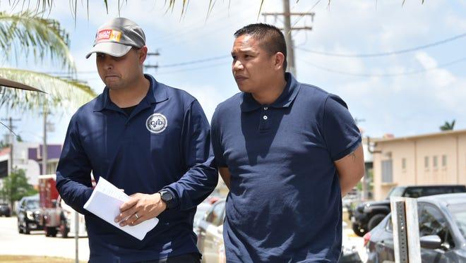 Nicolas T. Dela Cruz is escorted to the Guam Police Department Hagåtña precinct upon his arrest on Wednesday, April 20.