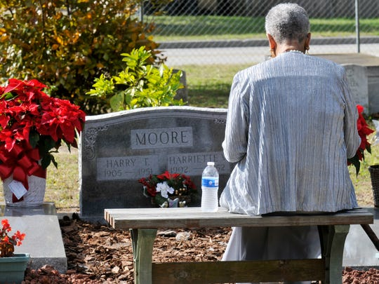 Moore sits on a bench near the grave of her mother