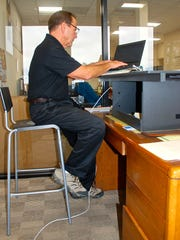 Bill Anderson can stand or sit while using one of Anderlyn Desk Company's desks. He built the desk prototype after experiencing neck pain while working at a regular desk.