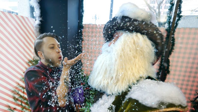 Dewey Rice of Rochester blows and sprinkles artificial snowflakes on a Santa that will be part of the display in the corner window of CGI Communications.