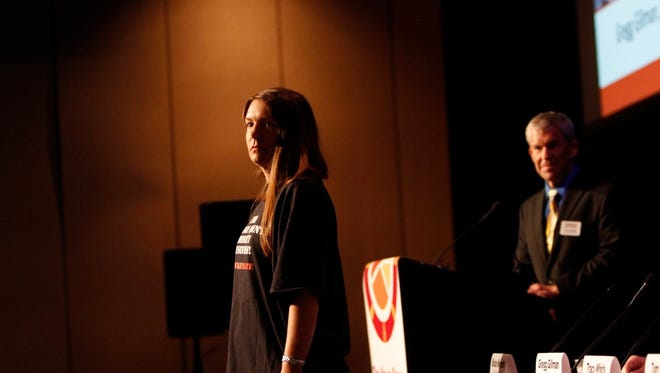 Jessica Thomas takes the stage at The News-Press Regional Economic Development Summit, protesting  Hendry County's monkey farms Monday, May 11 in Fort Myers.