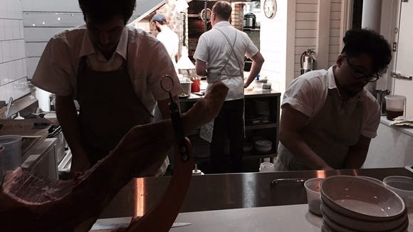 Chef and owner of The Anchorage, Greg McPhee oversees the activity in the kitchen during a soft opening.