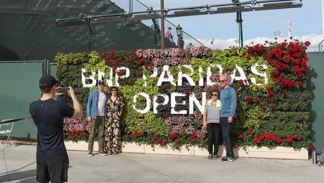 People pose for photos in front of a 24-foot flower wall inside the Indian Wells Tennis Garden installed by Eventscape International for the BNP Paribas Open. (March 2018)
