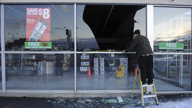 In this Nov. 30, 2018, file photo, Dennis Keeling, of Instant Services, measures for a broken window at an auto parts store following an earthquake in Anchorage.