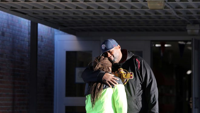 Dwayne Murray, director of Mt. Vernon Junior Knights basketball, consoles his step-daughter Leara Ashley Branch after the service for Shamoya McKenzie at Mount Vernon High School Jan. 1, 2017. Basketball standout Shamoya McKenzie, 13, was killed by a stray bullet on New Year's Eve when traveling in the passenger seat of her mother's car. The community, her teammates, friends and family gathered to remember at the high school.