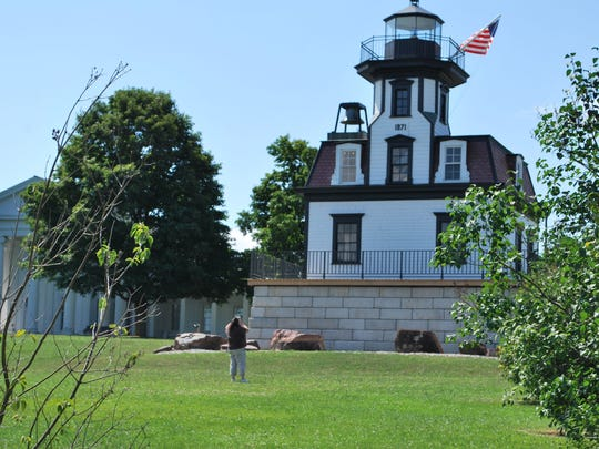 Tina Briston of Canton, NY takes a picture of the lighthouse at Shelburne Museum in Shelburne on July 29. Tina and Carl Bristol came from Canton, NY for a quick get-away. Tina collects teddy bears and lighthouses. Their next stop is the Teddy Bear Factory and then The Church Street Market Place.