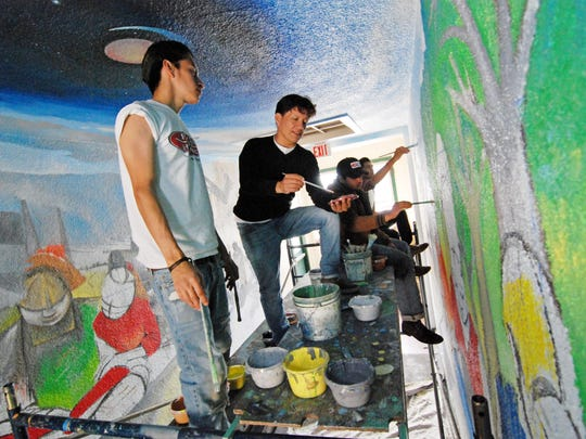 Josué David Rubio, left, of Hijos del Sol, on the scaffold with Jose Ortiz, center. At work behind Ortiz are José Nolasco and Luis Aguilar.