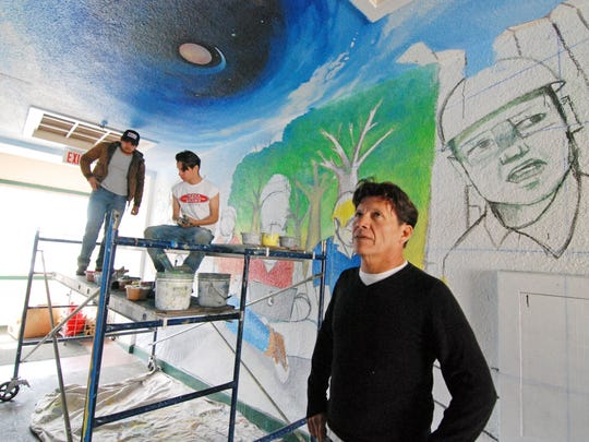 Jose Ortiz checking the progress of a new mural at Roosevelt School, tentatively named The Portal. Behind him on the scaffold are fellow artists José Nolasco, left, and Josué David Rubio