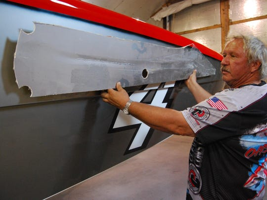 Ed Smith holds up a piece of the hull of the Cleveland Construction boat that was damaged during an offshore powerboat race in Marathon, Florida. Smith will be competing in the St. Clair River Classic.
