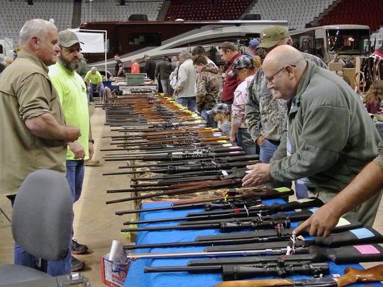 Clerks stand by as patrons (right) look over some of the rifles for sale at the State Fair of Louisiana Boat, Sport & RV, Gun Show and Bass Tournament at Hirsch Coliseum January 18, 2014