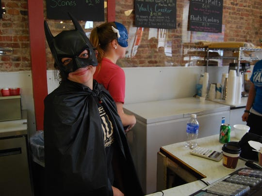 Miranda Hency dishes out ice cream at The Vault Ice Cream and Sweet Shoppe while dressed in a cape and cowl.