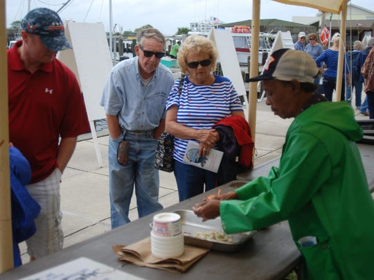 Shelia Ames shows how to properly clean a crab during Dock Day on the Bay.
